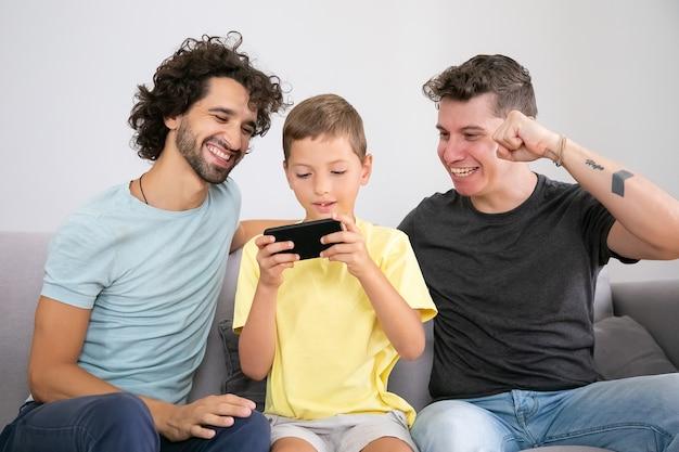 Aufgeregter junge spielt spiel auf dem handy, seine zwei glücklichen väter sitzen in seiner nähe und helfen. vorderansicht. familie zu hause und kommunikationskonzept