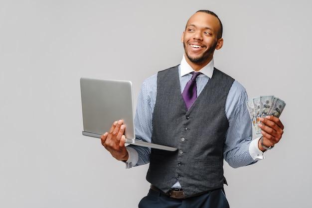 Aufgeregter junger afroamerikanermann, der bargeld und laptop über hellgrauer wand hält