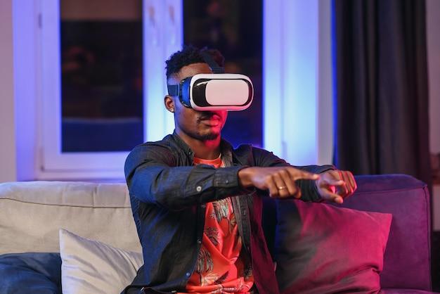 Aufgeregter junger afroamerikanischer mann, der hand nach vorne ausdehnt, unter verwendung des virtual-reality-headsets, das auf bett sitzt, kopiert raum