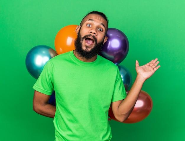 Aufgeregter junger afroamerikanischer typ mit grünem t-shirt, der vor ballons steht und die hand isoliert auf grüner wand ausbreitet