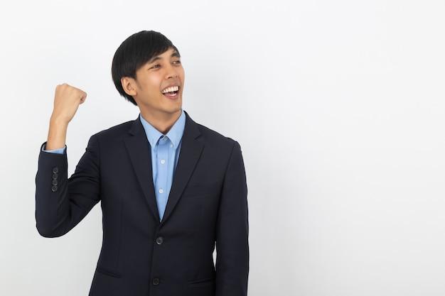 Aufgeregter junger asiatischer geschäftsmann, der seine fäuste mit dem glücklichen begeisterten gesicht, erfolg feiernd anhebt