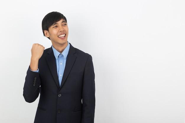 Aufgeregter junger asiatischer mann des geschäfts, der seine fäuste mit dem glücklichen begeisterten gesicht, den erfolg lokalisiert auf weiß feiernd anhebt
