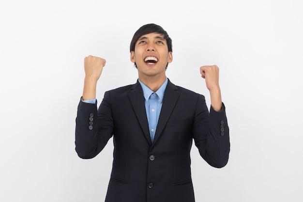 Aufgeregter junger asiatischer mann des geschäfts, der seine fäuste mit dem glücklichen begeisterten gesicht, den erfolg lokalisiert auf weißer wand feiernd anhebt.