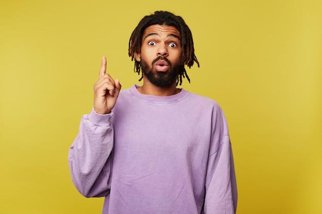 Aufgeregter junger attraktiver dunkelhäutiger brünetter mann gekleidet in der freizeitkleidung, die zeigefinger mit ideenzeichen hebt und emotional augenbrauen hochzieht und über gelbem hintergrund aufwirft