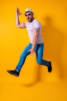Aufgeregter junger bärtiger fitness-sportler mit hut und sonnenbrille springt sehr emotional isoliert auf gelb