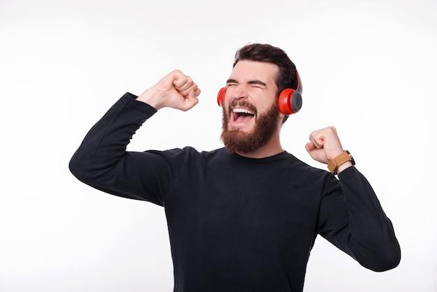 Aufgeregter junger bärtiger mann, der musik an drahtlosen kopfhörern hört