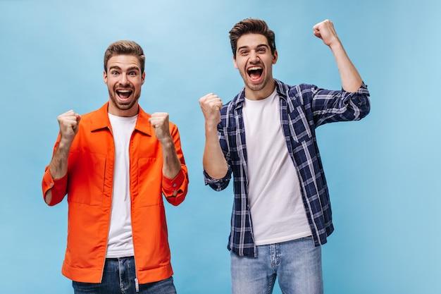 Aufgeregter junger bärtiger mann in orangefarbener jacke und sein freund im karierten hemd freuen sich und lächeln an der blauen wand.
