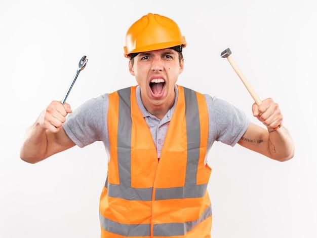Aufgeregter junger baumeister in uniform, der hammer mit gabelschlüssel hält