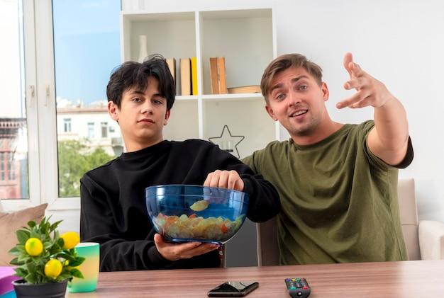 Aufgeregter junger blonder hübscher kerl schaut und zeigt auf kamera mit hand, die am tisch mit jungem brünettem hübschem kerl sitzt, der schüssel chips innerhalb des wohnzimmers hält