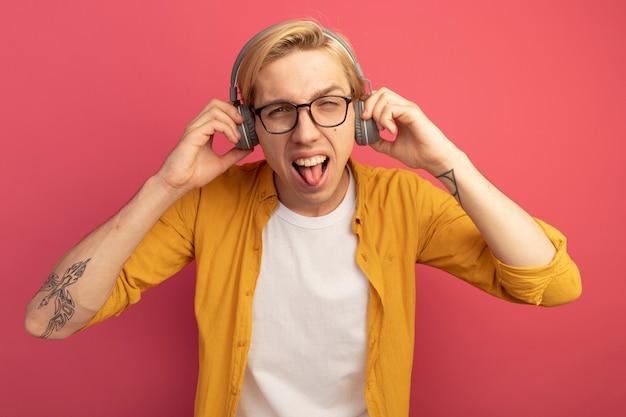 Aufgeregter junger blonder kerl, der geradeaus schaut und gelbes t-shirt und brille mit kopfhörern trägt, die auf rosa lokalisiert werden