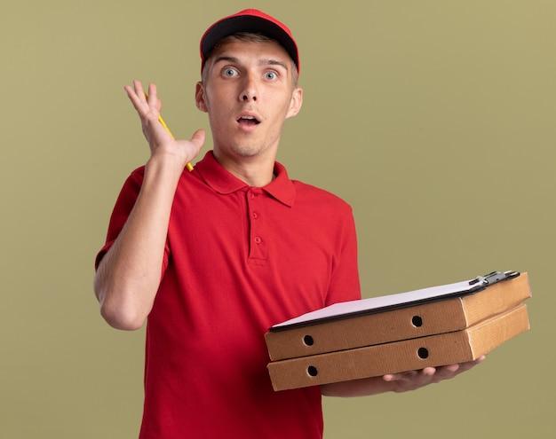 Aufgeregter junger blonder lieferjunge steht mit erhobener hand und hält klemmbrett auf pizzaschachteln auf olivgrün