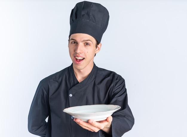 Aufgeregter junger blonder männlicher koch in kochuniform und mütze, der die hand hinter dem rücken hält und auf die kamera schaut, die die platte in richtung kamera ausstreckt, isoliert auf weißer wand