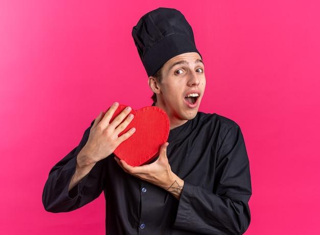 Aufgeregter junger blonder männlicher koch in kochuniform und mütze, die herzform mit beiden händen hält