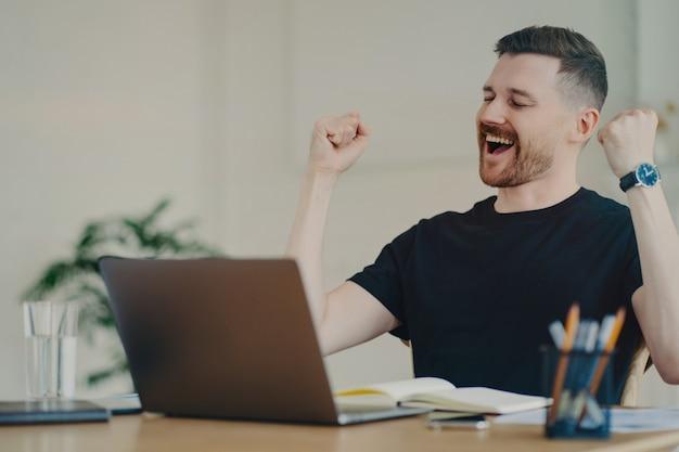 Aufgeregter junger freiberufler oder geschäftsmann, der eine gewinnende oder glückliche geste zeigt, die sein glück zeigt und den erfolgreichen deal während des videoanrufs feiert, der am tisch im büro oder zu hause sitzt