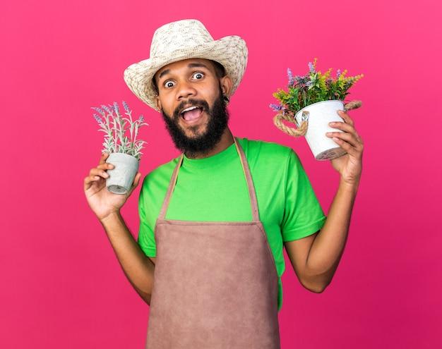 Aufgeregter junger gärtner afroamerikanischer typ mit gartenhut, der blumen im blumentopf hält