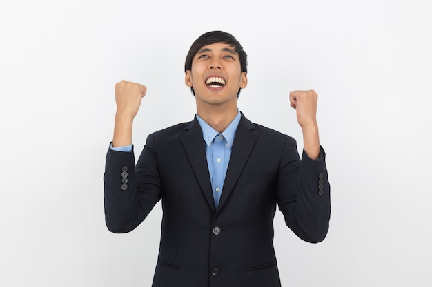 Aufgeregter junger geschäftsasiatischer mann, der seine fäuste mit glücklich entzücktem gesicht hebt und erfolg feiert