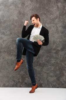 Aufgeregter junger geschäftsmann, der geld hält, macht gewinnergeste.