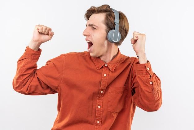 Aufgeregter junger gutaussehender kerl, der rotes hemd mit kopfhörern trägt, die ja-geste einzeln auf weißer wand zeigen