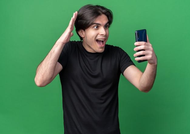 Aufgeregter junger gutaussehender kerl mit schwarzem t-shirt, der das telefon isoliert auf grüner wand hält und betrachtet