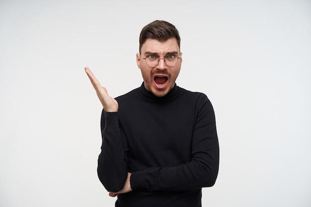 Aufgeregter junger gutaussehender kurzhaariger brünetter kerl in brille, der emotional seine handfläche hebt, während er mit geöffnetem weitem mund kreuzend aussieht und auf weiß posiert