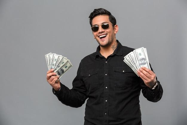 Aufgeregter junger gutaussehender mann, der geld hält.
