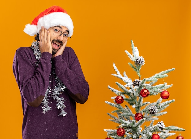 Aufgeregter junger hübscher kerl, der nahe weihnachtsbaum steht, der weihnachtshut mit girlande am hals trägt, die hände auf wangen lokalisiert auf orangefarbenem hintergrund setzen