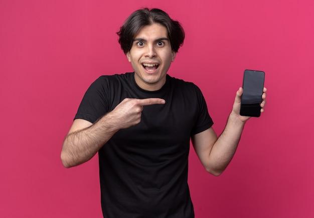 Aufgeregter junger hübscher kerl, der schwarzes t-shirt hält und auf telefon lokalisiert auf rosa wand hält