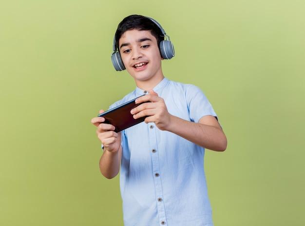 Aufgeregter junger kaukasischer junge, der kopfhörer trägt spiel auf handy lokalisiert auf hintergrund mit kopienraum