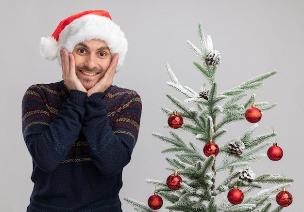 Aufgeregter junger kaukasischer mann, der weihnachtshut trägt, der nahe weihnachtsbaum steht, hält hände auf gesicht, das kamera lokalisiert auf weißem hintergrund betrachtet