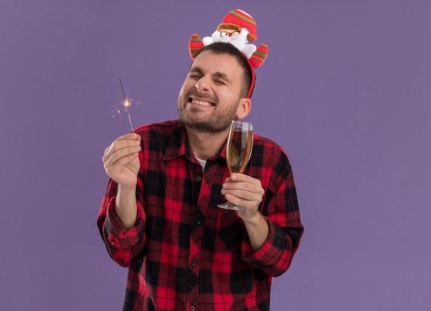 Aufgeregter junger kaukasischer mann, der weihnachtsmann-stirnband hält, das feiertagswunderkerze und glas champagner lächelnd mit geschlossenen augen lokalisiert auf lila hintergrund trägt