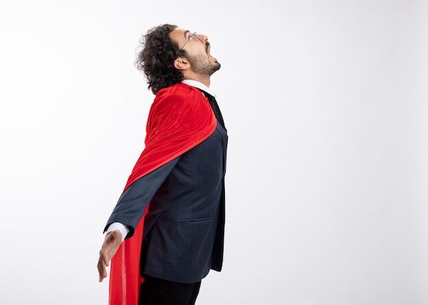 Aufgeregter junger kaukasischer superheldenmann in optischer brille, der anzug mit rotem mantel trägt, steht seitlich nach oben