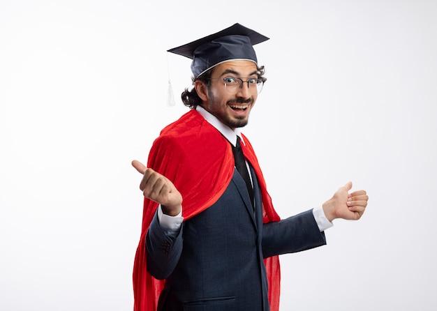 Aufgeregter junger kaukasischer superheldenmann in optischer brille, der anzug mit rotem mantel und abschlusskappe trägt, steht seitlich und zeigt auf die seiten