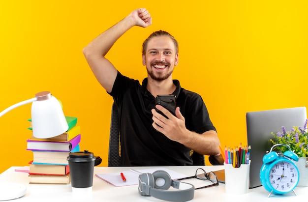 Aufgeregter junger kerl, der am tisch mit schulwerkzeugen sitzt und das telefon hält, das eine ja-geste zeigt