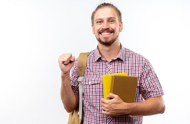 Aufgeregter junger kerl, der einen rucksack trägt und bücher hält, die eine ja-geste zeigen, die auf weißer wand mit kopienraum isoliert ist?