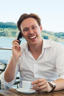 Aufgeregter junger lachender mann bei der unterhaltung am telefon
