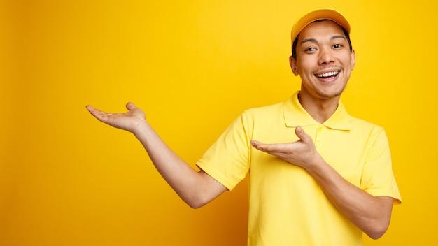 Aufgeregter junger lieferbote, der mütze und uniform trägt, zeigt mit den händen zur seite