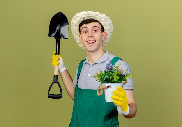 Aufgeregter junger männlicher gärtner, der gartenhut und handschuhe trägt, hält spaten und blumen im blumentopf