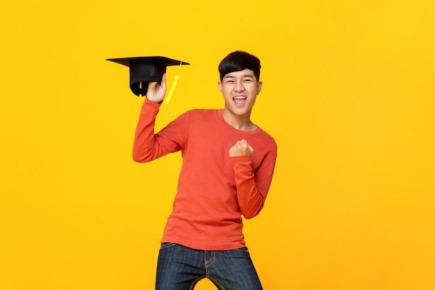 Aufgeregter junger männlicher student, der eine staffelungskappe tut geschlossene faustgeste hält