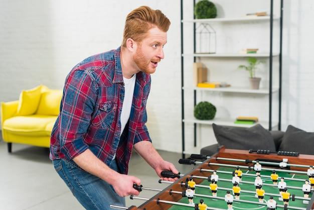 Aufgeregter junger mann, der das fußballtischfußballspiel im wohnzimmer spielt