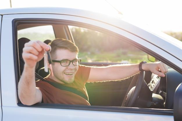 Aufgeregter junger mann, der einen autoschlüssel in seinem neuen fahrzeug zeigt.