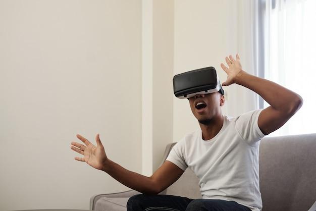 Aufgeregter junger mann, der gruseliges spiel in der brille der virtuellen realität spielt