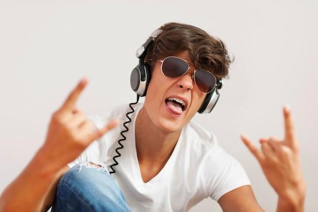 Aufgeregter junger mann, der harte rockmusik hört