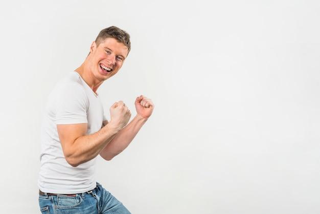 Aufgeregter junger mann, der ihre faust gegen weißen hintergrund zusammenpreßt