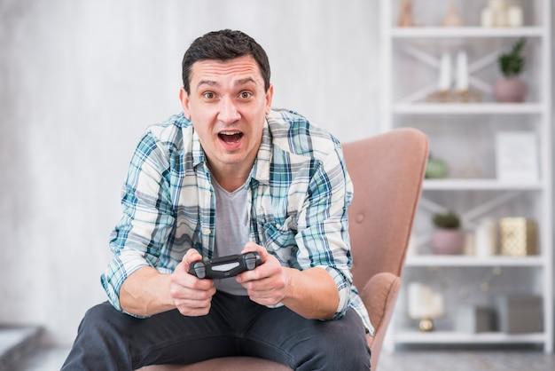 Aufgeregter junger mann, der im lehnsessel sitzt und mit gamepad spielt
