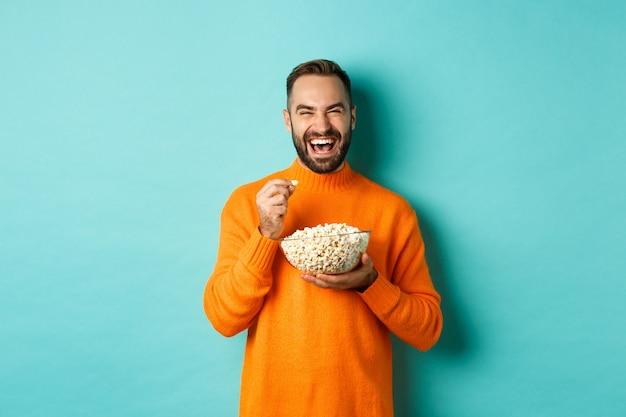 Aufgeregter junger mann, der interessanten film auf fernsehbildschirm sieht, popcorn isst und erstaunt aussieht