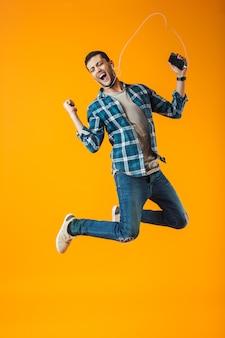 Aufgeregter junger mann, der kariertes hemd trägt, das lokal über orange hintergrund springt und musik mit kopfhörern und handy hört