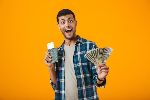Aufgeregter junger mann, der kariertes hemd trägt, das lokal über orange hintergrund steht, geldbanknoten zeigt, pass mit flugtickets hält