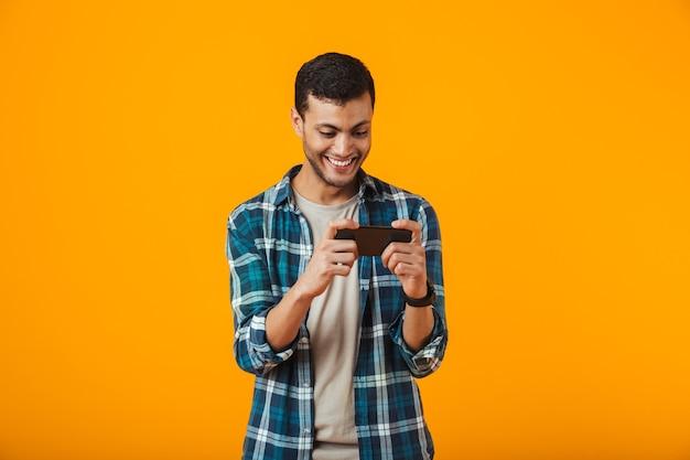 Aufgeregter junger mann, der kariertes hemd trägt, das lokal über orange hintergrund steht und spiele auf handy spielt
