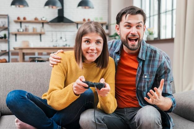 Aufgeregter junger mann, der mit ihrer frau spielt das videospiel sitzt
