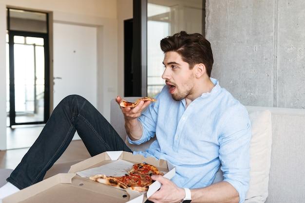 Aufgeregter junger mann, der tv-fernbedienung hält
